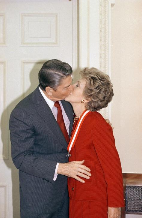 President Ronald Reagan and First Lady Nancy Reagan share a kiss {photo: news.wabe.org}