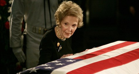 File photo of former U.S. first lady Nancy Reagan touching the casket of her husband former U.S. President Ronald Reagan as it lies in state on Captol Hill in Washington