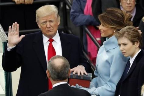 Donald Trump takes the oath of office with his wife Melania and son Barron at his side, during his inauguration at the U.S. Capitol in Washington